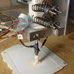 A 3D printer creates a small dildo.
