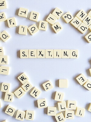 Scrabble letters spell out sexting.