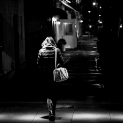 A lady walking in a dark street