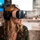 A young woman wears a virtual reality headset.