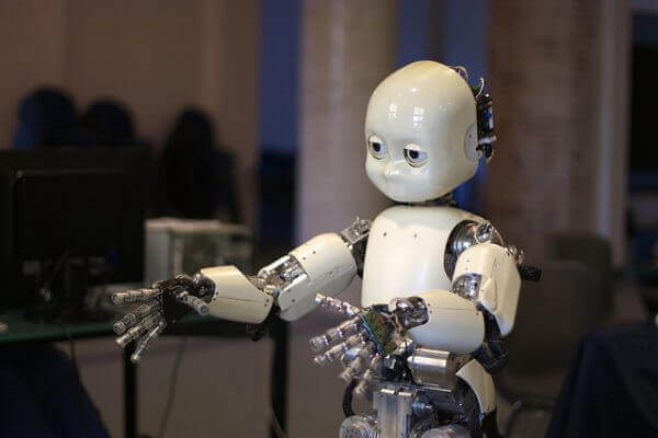 The photo displays iCub, a child-like humanoid robot.