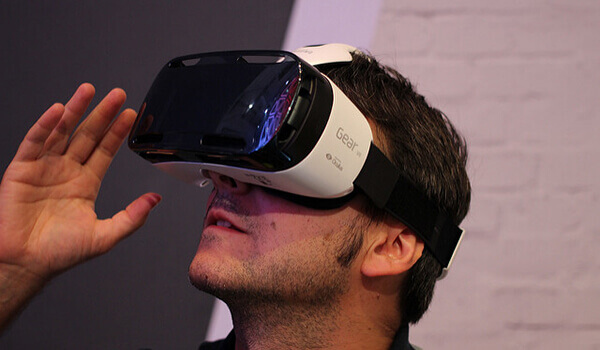 A man wears a Samsung Gear VR headset.