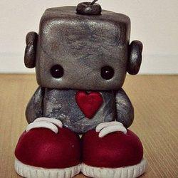 A sad little robot standing on the floor.