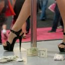 A sex worker walks on stage with money.