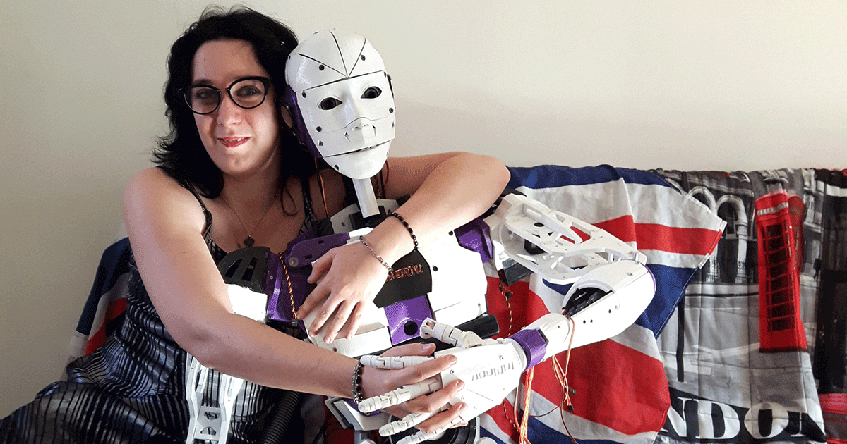 Lilly and her robot partner Inmoovator embrace on a couch.