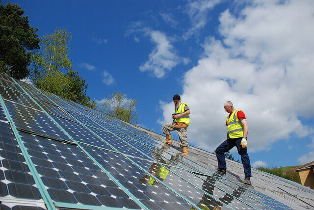 Workers walks across slanted solar panels.