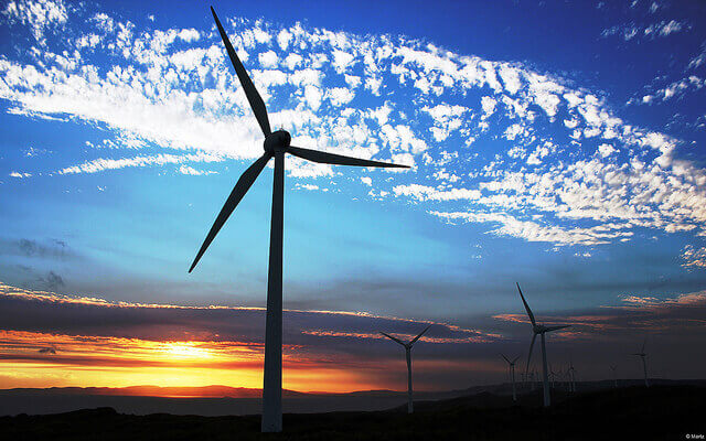A wind turbine appears over a sunset horizon.