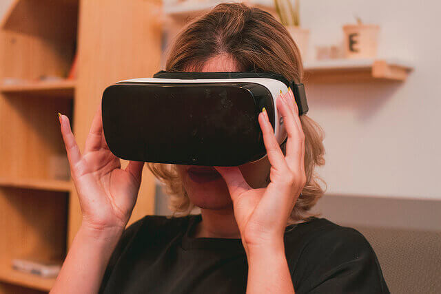 A woman sits wearing a VR headset.