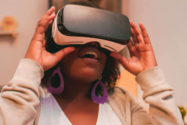 A young woman smiles while wearing a VR headset.