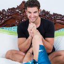 A man sits on a bed giving his girlfriend a foot massage.