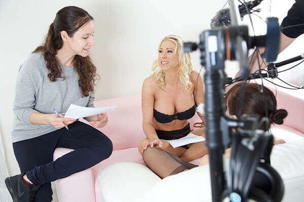 A director of a VR sex therapy session speaks to an adult actress in front of a camera.