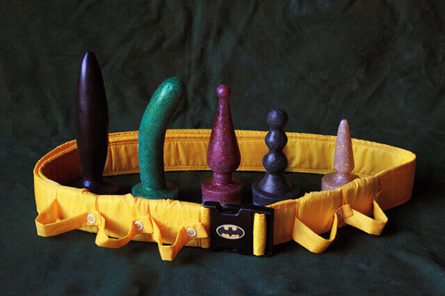Glittery silicone phallic sex toys with a batman utility belt.
