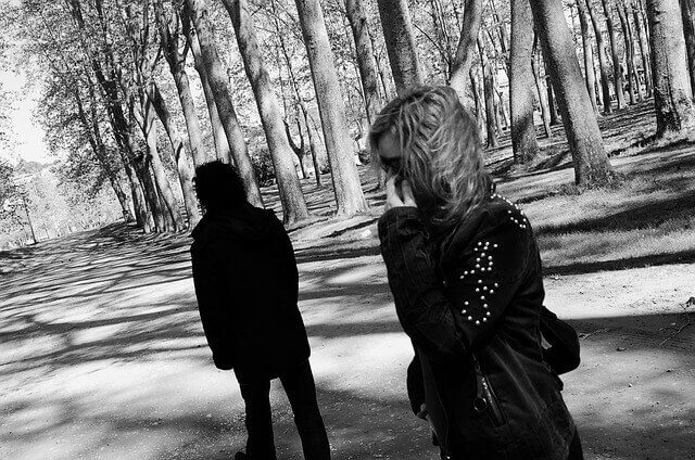 A couple appear on a forest trail looking distant from each other.