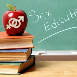 "An apple with male and female symbols carved into it appears in front of a chalkboard that says ""Sex Education."""