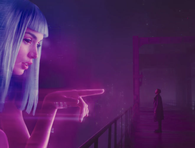 AI companion Joi reaches out to the character K from a billboard ad in the movie Blade Runner 2049.