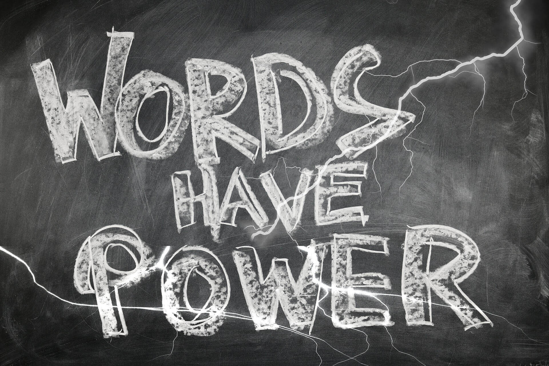 """Words have power"" written in white chalk and in all caps appears on a blackboard."