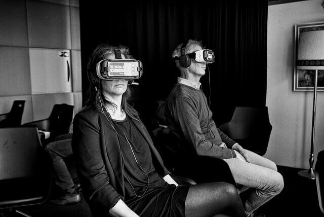 Two people sit wearing VR headsets.
