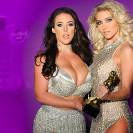 Adult performers Angela White and Harli Lotts wear sliver dreses and hole an award in front of a purple background.