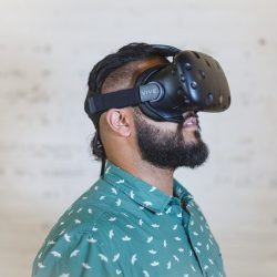 A bearded man with a green shirt wears a VR headset.