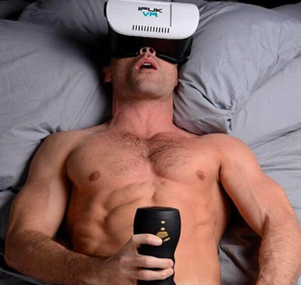 A man without a shirt wears a VR headset whhile lying down and holds a male masturbator in one hand.