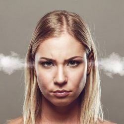 A blonde woman looks annoyed and has steam coming out of her ears.