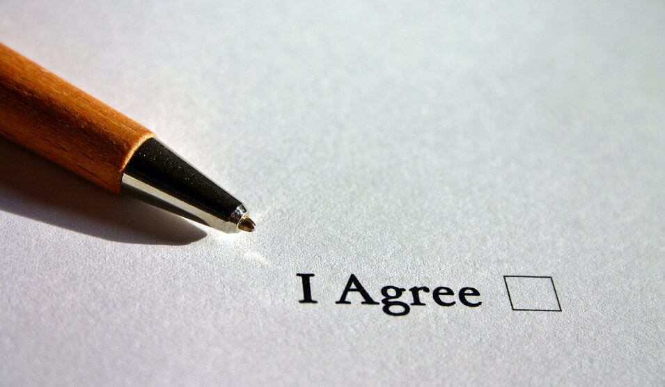 "A pen lies next to a checkbox with the words ""I Agree"" next to it."