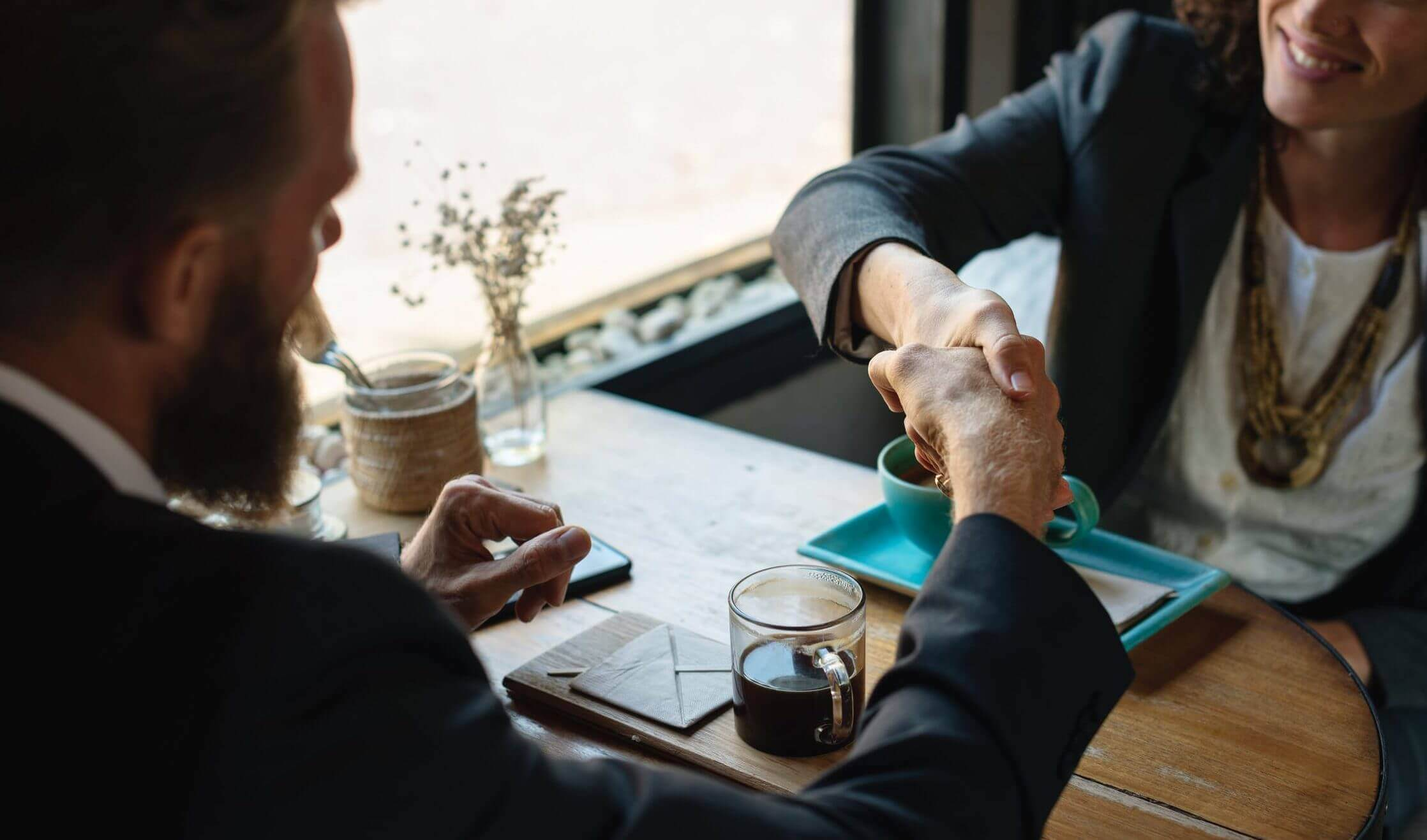 Two business people shake hands while sitting down at a coffee shop table.