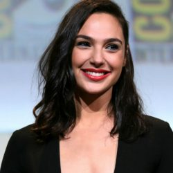 Actress Gal Gadot wears a dark top and smiles wearing red lipstick.