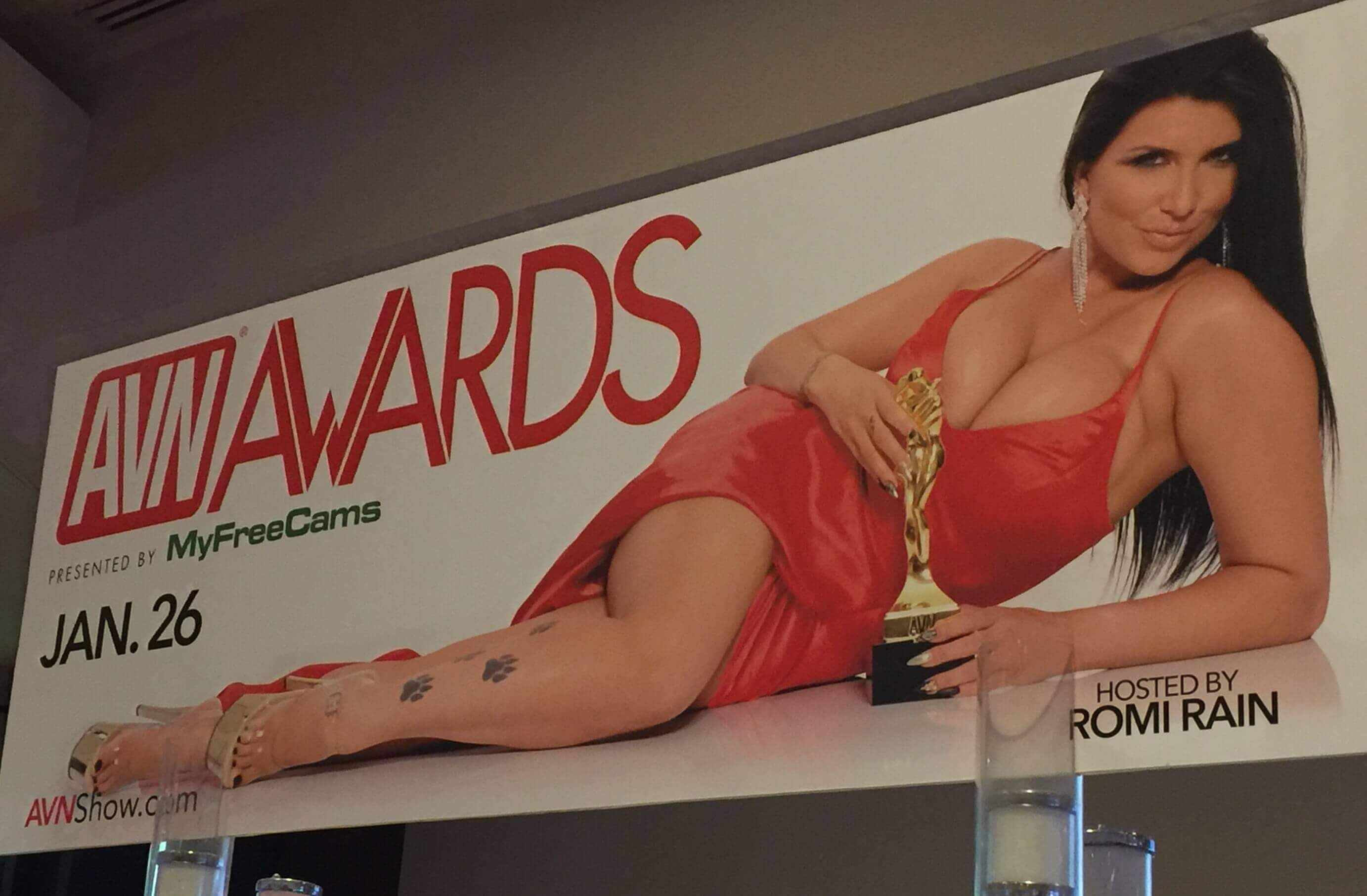 A brunette woman wearing a revealing orange dress lies on her side with an gold awards trophy next to the text AVN Awards 2019.