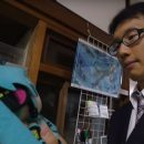 Japanese man holds a stuffed animal versions of his hologram wife.