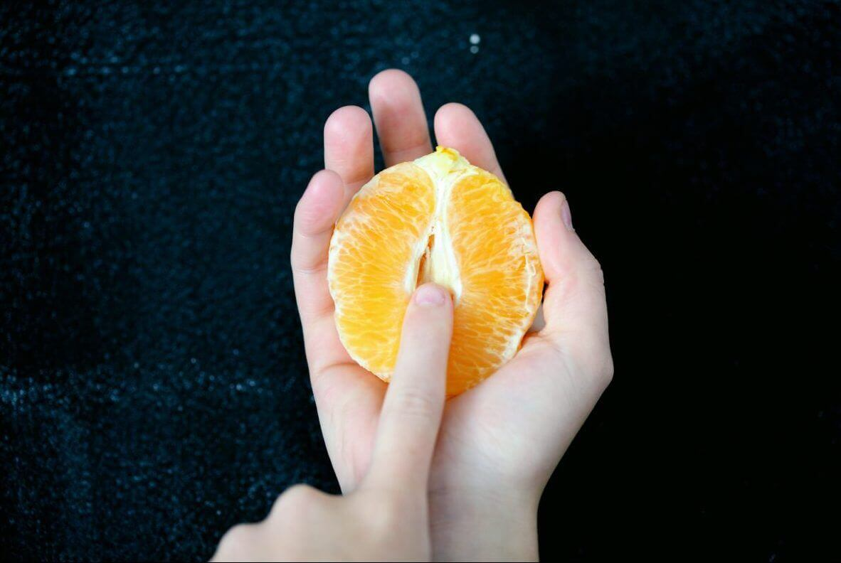 One hand holds a peeled orange split in half while the finger of the other hand strokes the inside cavity.