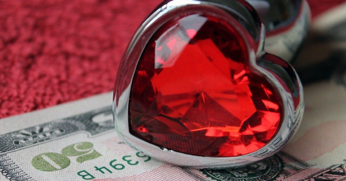 A red and sliver heart-shaped sex toy lies on a US$50 bill ontop of red fabric.