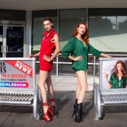 Two young women stand in platform heels posting next to bus benches showing ads for out of work strippers.