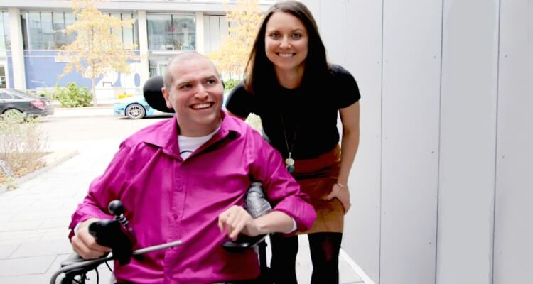 Andrew Gurza in a wheelchair next to sister Heather Morrison