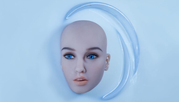 Kokeshis face and head, without hair, appears in a bath of white fluid.