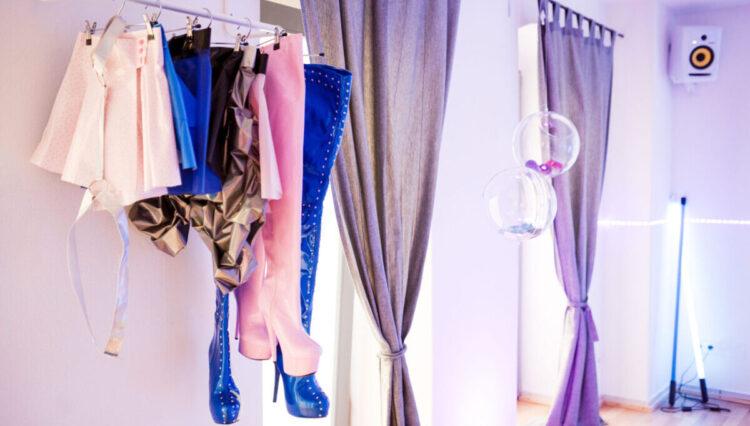 La habitación de Kokeshis muestra zapatos colgados y cortinas moradas sobre ventanas altas.