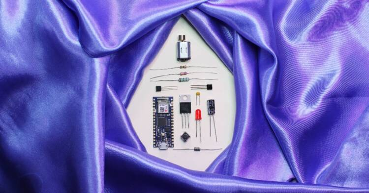 A purple satin sheet encircles disassembled electronic parts.