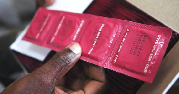 A man's hand shown holding a line of condoms.