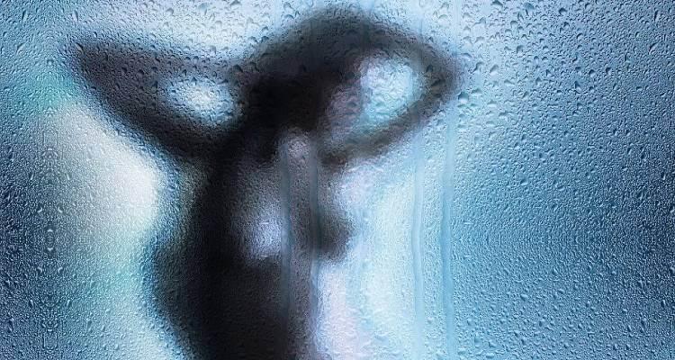 Screenshot of a women taking bath beyond a shower screen