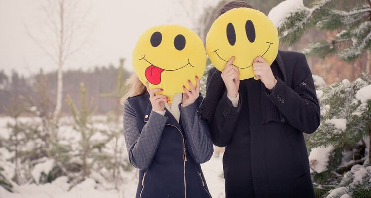 Image of Couple Holding Smiley over their Face in Cold Winter