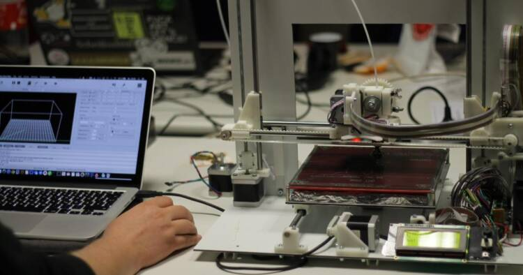 Image of a man working on laptop and 3D printer