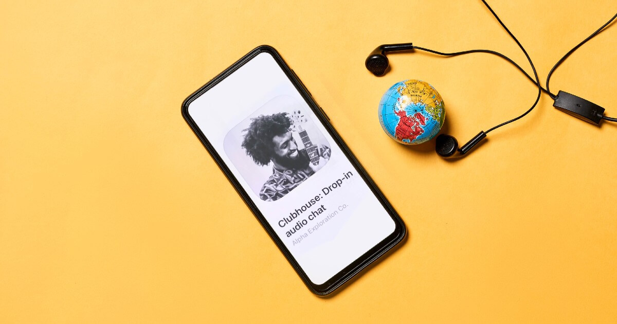 Clubhouse Invite-only Audio Chat App Open in Mobile Phone with a Globe and Earphone Display in Background