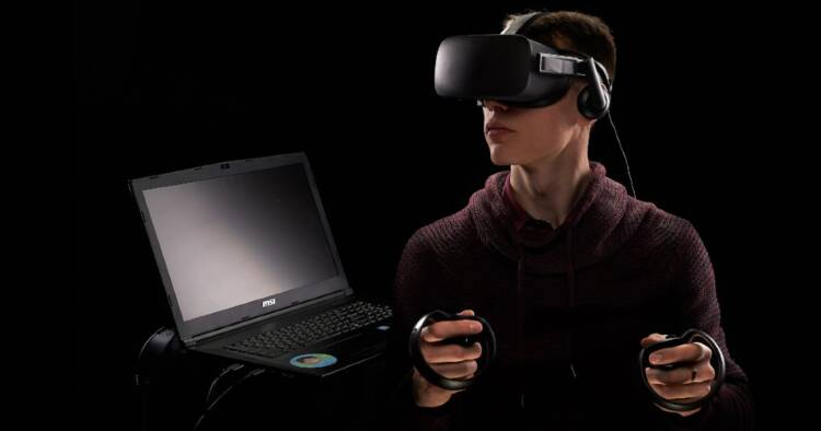 Image of a man using virtual reality devices and laptop