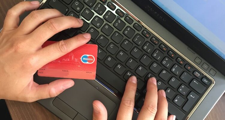 Hands with credit card on computer keyboard