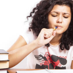 Woman studies with textbooks and notebook