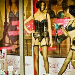 2 mannequin in lingerie displaying sex toys in window shopping area of a store