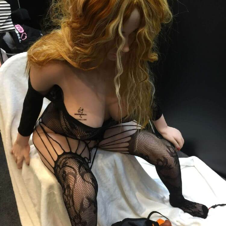 Picture of MissDoll in lingerie sitting for photoshoot with sex toys displayed right in front