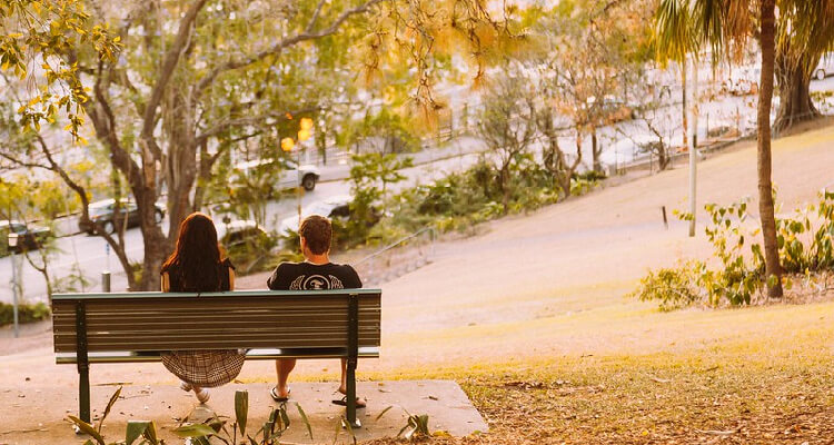 Two people on a bench with their backs facing the camera (attribution: Andrew S)