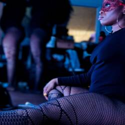 A dancer in fishnet stockings sits in front of a lighted mirror while other coworker getting ready