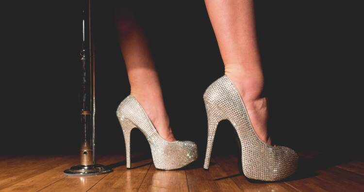 Image of beautiful legs with high-heels standing besides bar